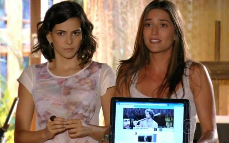 Mila olha assustada enquanto que Carol mostra o notebook com a foto de Lino
