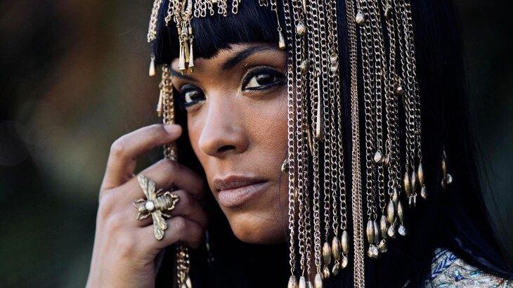 Lidi Lisboa caracterizada de Maalate, tocando acessório na cabeça