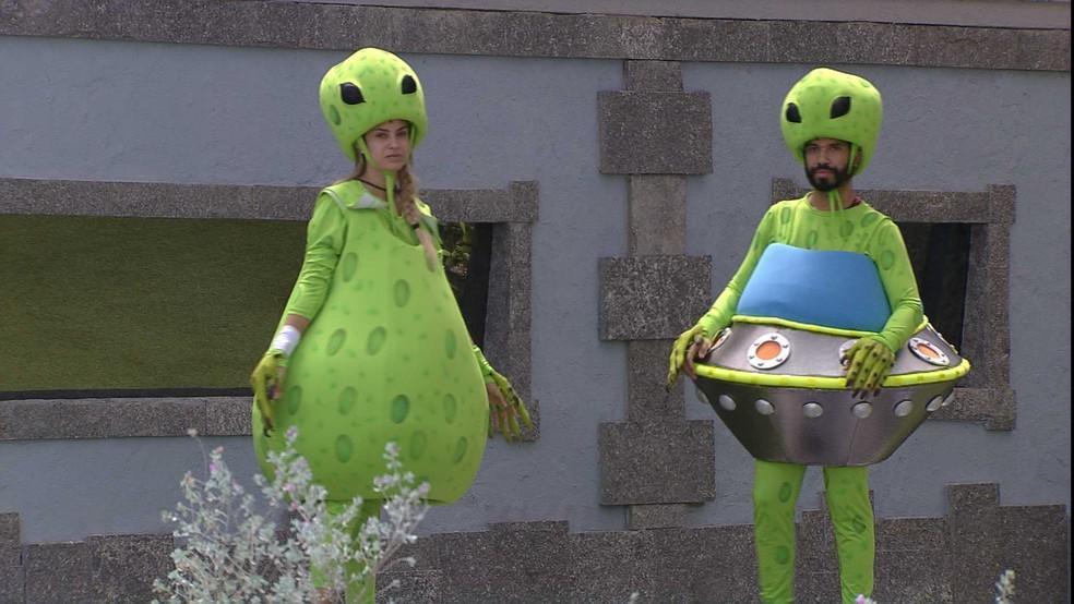 Sarah e Gilberto fantasiados de alienígenas no gramado do BBB21