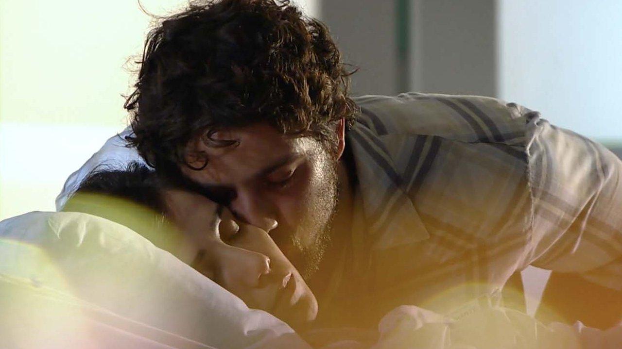 Rodrigo dá um beijo em Manu enquanto ela dorme em hospital