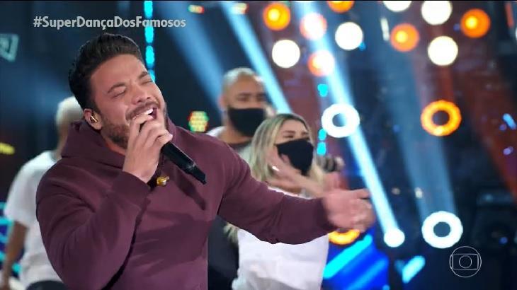Wesley Safadão cantando, com microfone na mão e o outro braço aberto. Ao fundo, bailarinas dançam na Super Dança dos Famosos