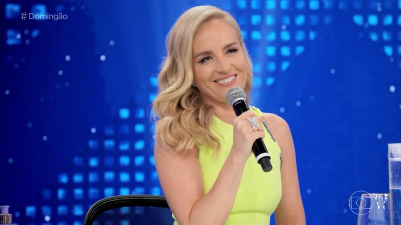 Angélica segurando o microfone e sorrindo no júri do Show dos Famosos