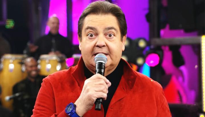 Faustão segurando o microfone durante seu programa na Globo