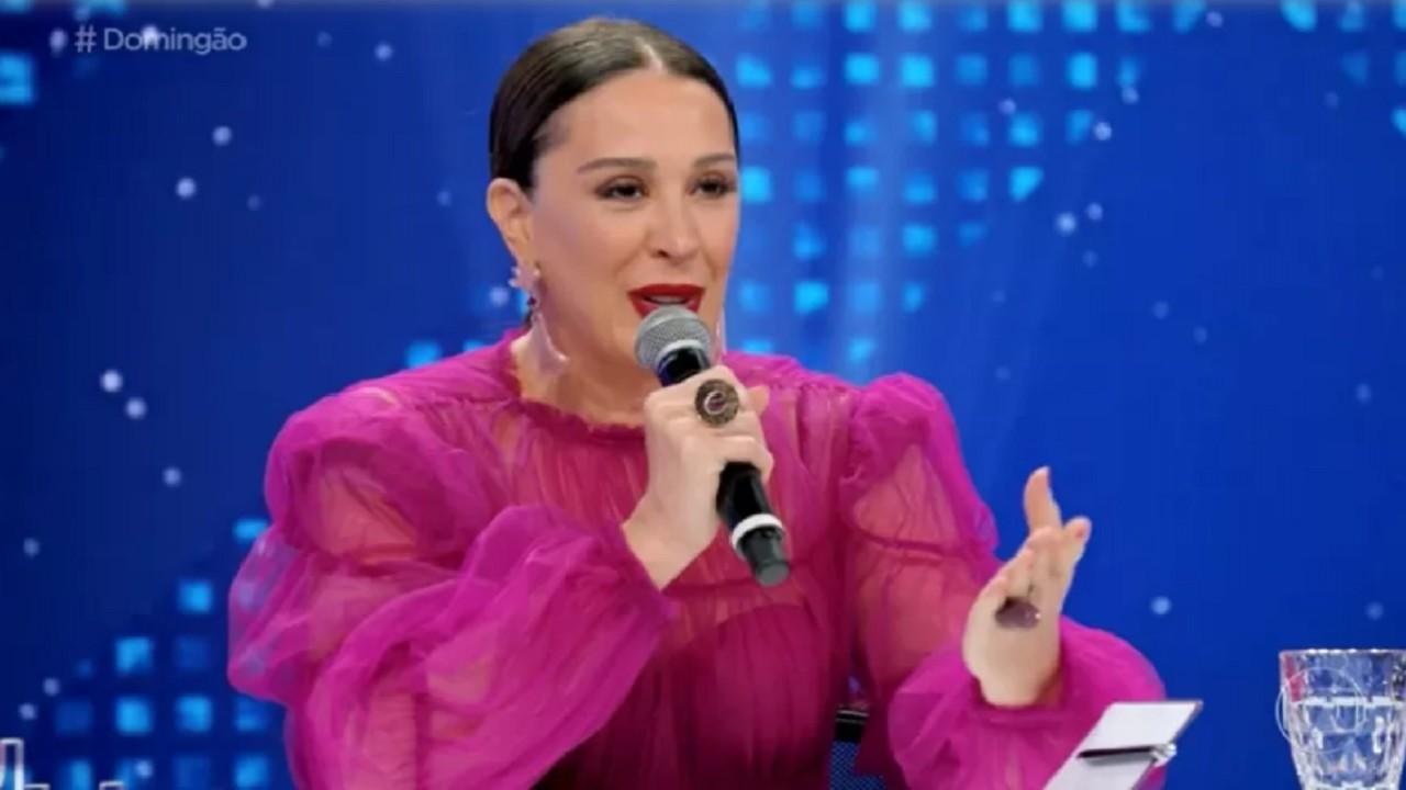 Claudia Raia sentada, segurando um microfone e falando durante o Show dos Famosos