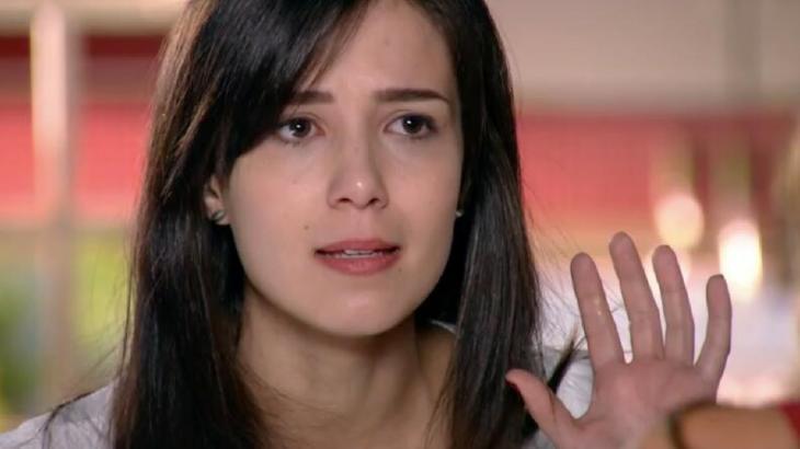 Manuela com expressão de raiva e a mão levantada