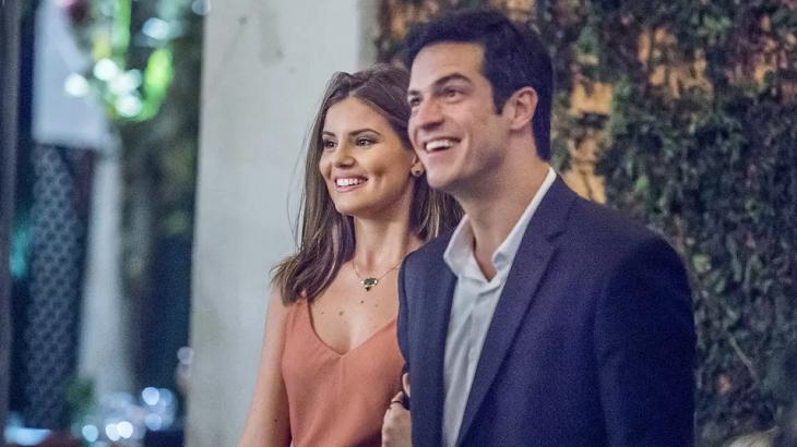 Cena de Pega Pega com os protagonista, Luíza e Eric de braços dados e sorrindo