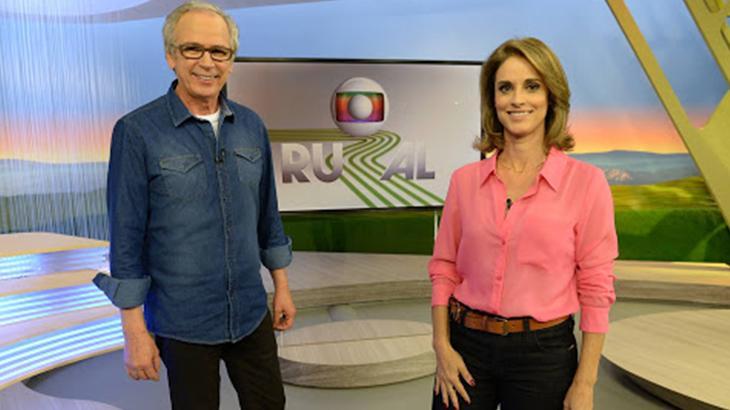 Apresentadores Helen Martins e Nélson Araújo sorrindo no cenário do Globo Rural