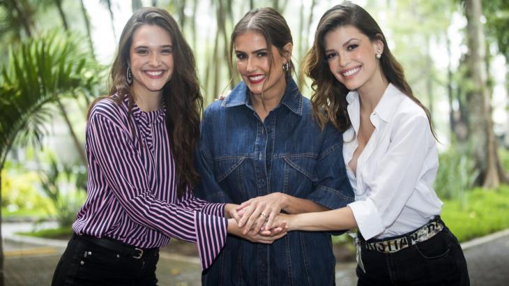 Luna, Alexia e Kyra de mãos dadas e sorrindo para a câmera