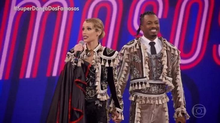 Juliana Didone de mãos dadas com o parceiro, vestido de toureiros na Super Dança dos Famosos
