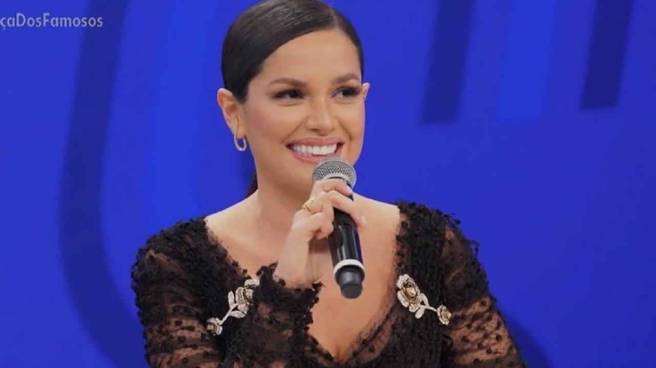 Juliette sorrindo, de microfone na mão e sentada