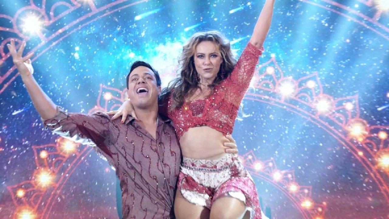 Paolla Oliveira no colo do dançarino, com as mãos erguidas