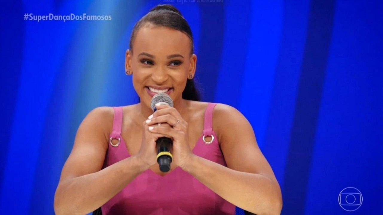 Rebeca Andrade sorrindo e segurando o microfone no júri da Super Dança dos Famosos