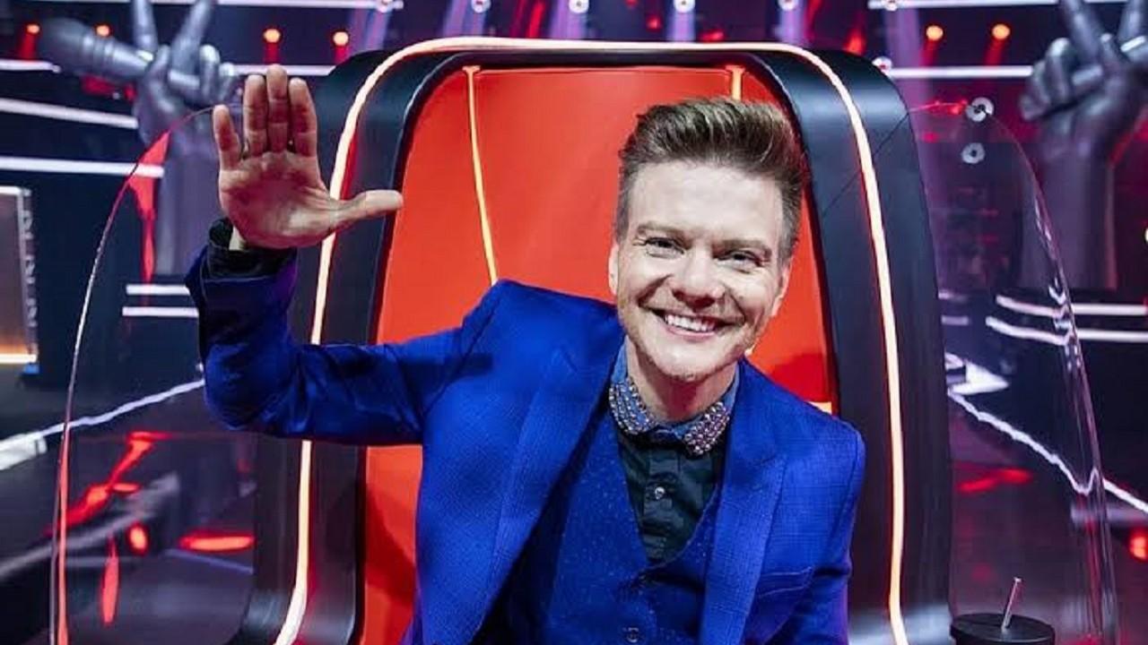 Michel Teló sorrindo e com a mão no botão do The Voice