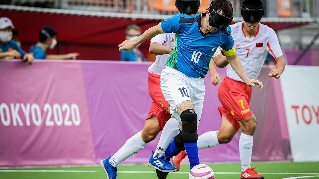 Jogador brasileiro de futebol do cinco dribla outros jogadores com a bola