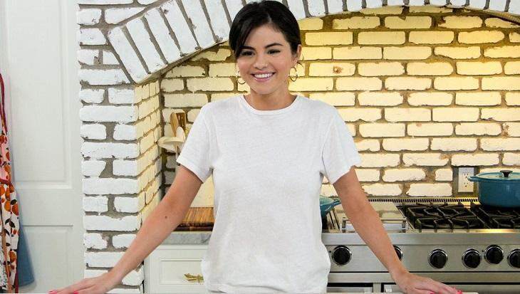 Selena Gomez com as mãos na bancada da cozinha e sorrindo