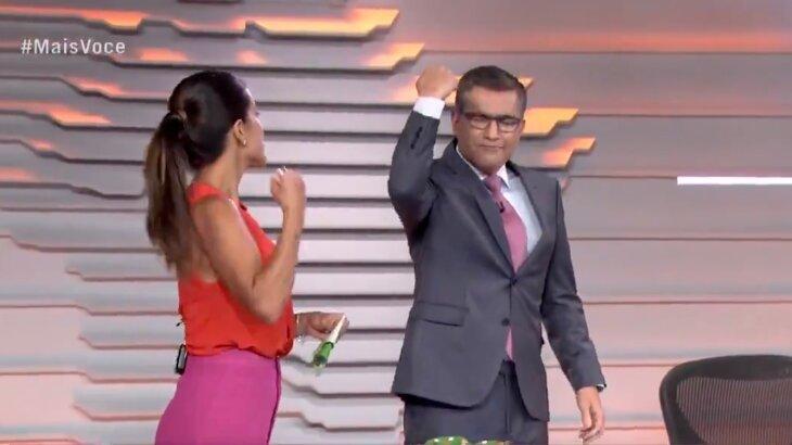 Helter Duarte vibrando, de olhos fechados e com o braço fechado, ao lado de Carol Barcellos