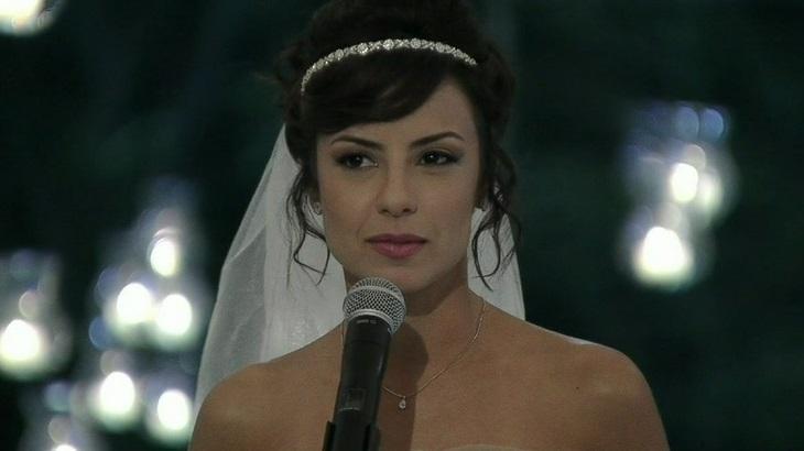 Cena de Império com Maria Clara vestida de noiva diante de um microfone