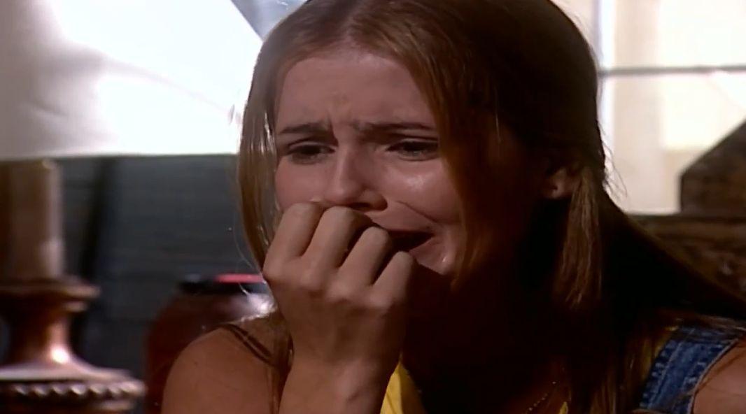 Iris com a mão na boca chorando