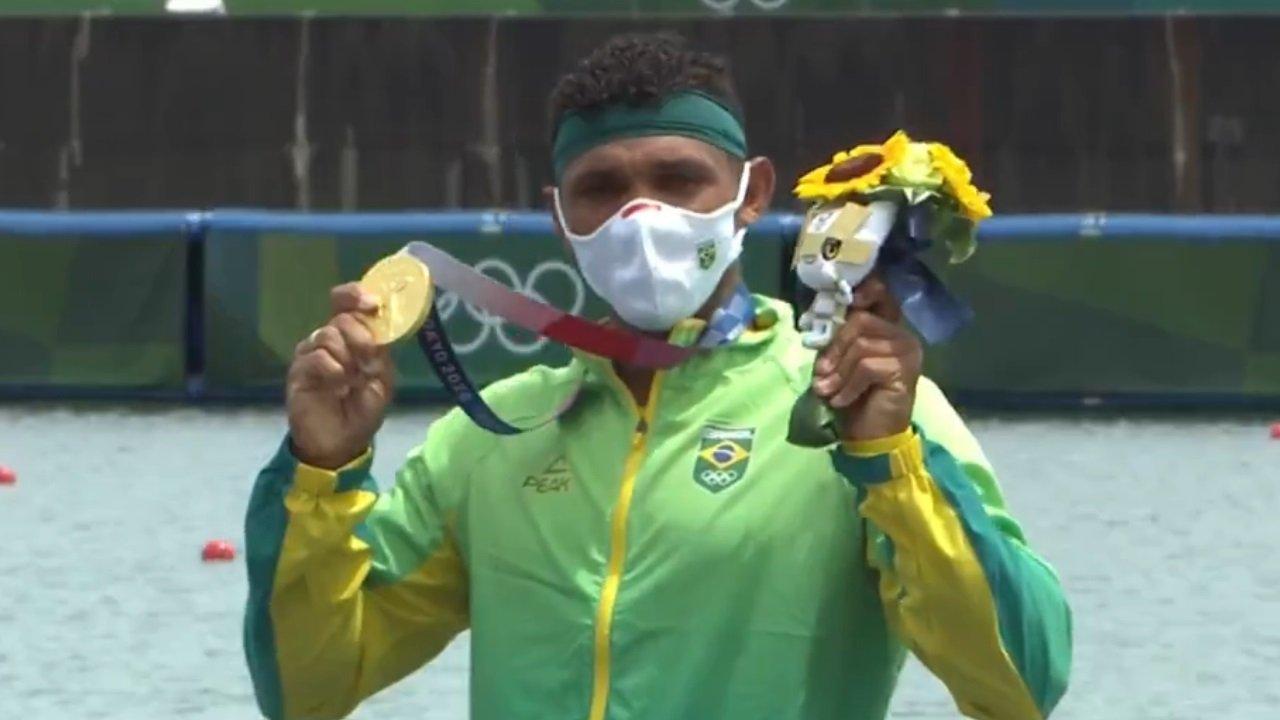 Isaquias Queiroz ergue a medalha de ouro no pódio da canoagem das Olimpíadas de Tóquio