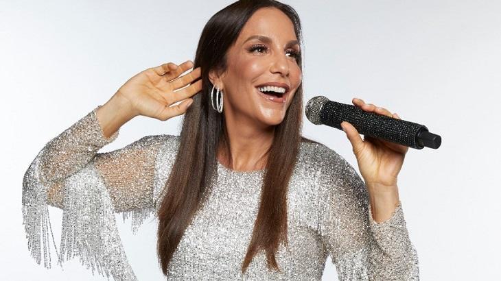 Ivete Sangalo com microfone na mão e cantando