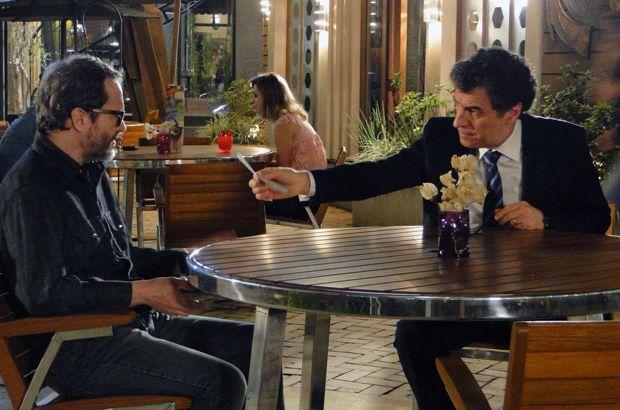 Jonas estende a mão segurando um cheque e o oferece a Lourenço