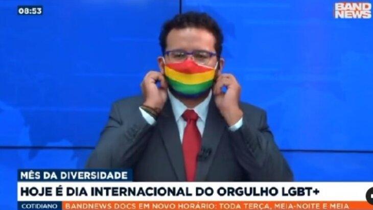 Juliano Dip colocando a máscara da bandeira do arco-íris durante jornal