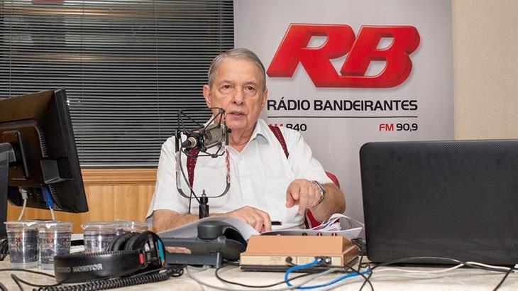 José Paulo de Andrade aparece em sua mesa de trabalho, falando ao microfone