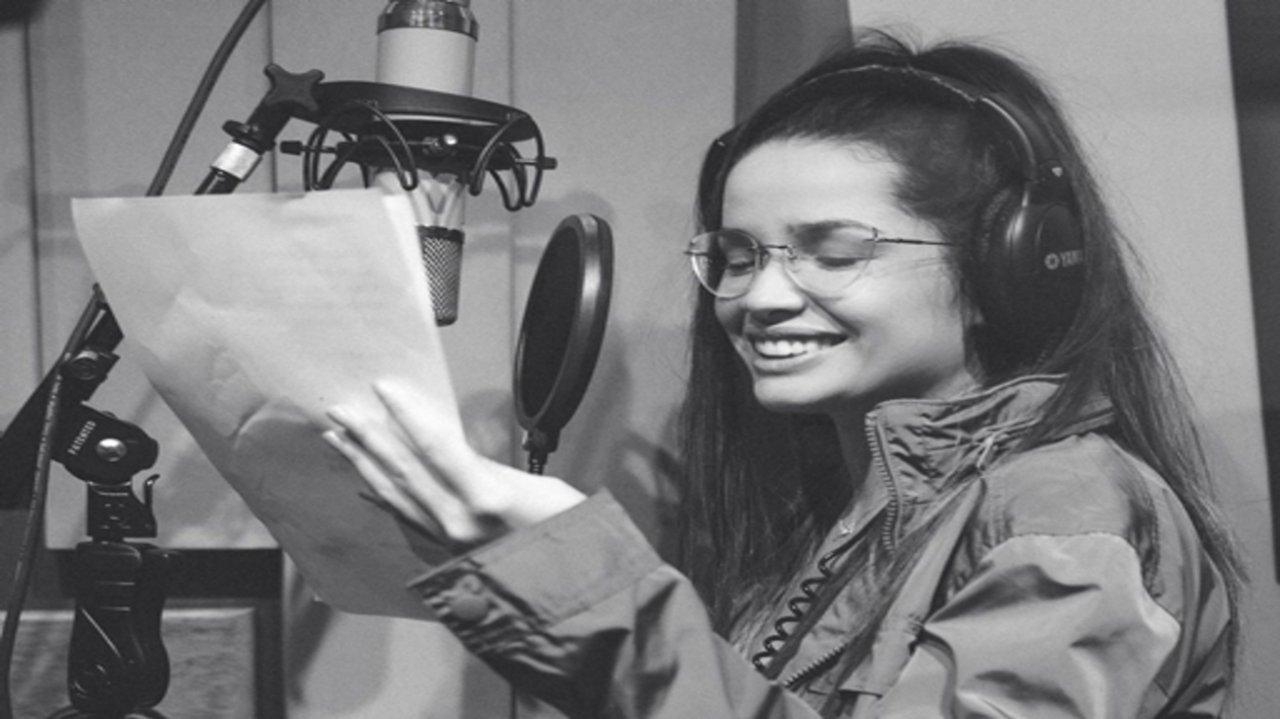 Juliette sorrindo e lendo no estúdio