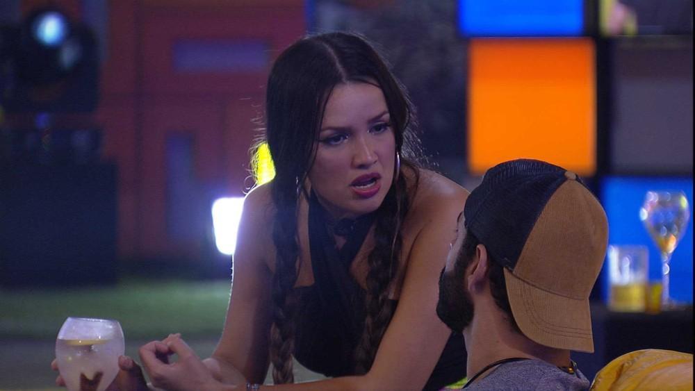 Juliette de traças e uma taça de bebida conversando ao lado de Rodolffo que está de boné de costas para a sister na festa do BBB21