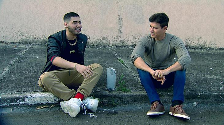 Kevinho sentado na calçada com Rodrigo Faro