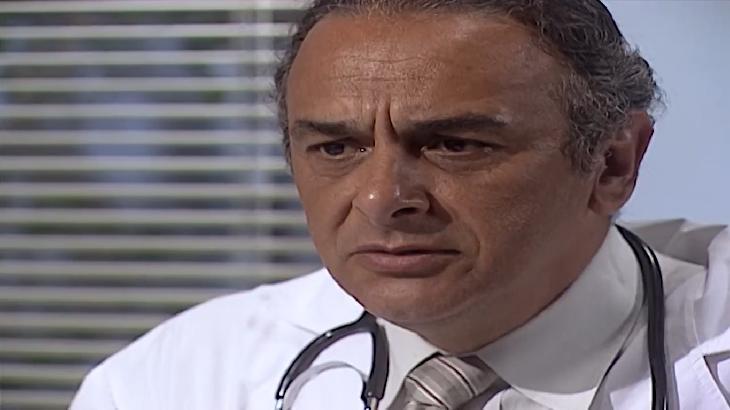 Cena de Laços de Família com Cesar com cara de sério, vestido como médico e com o estetoscópio no pescoço