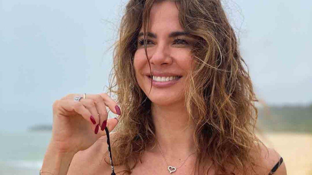 Luciana Gimenez na praia sorrindo e cabelo bagunçado