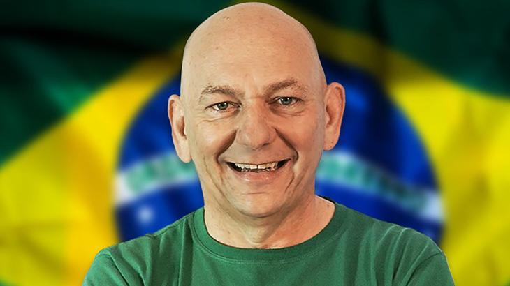 Luciano Hang posa para foto sorrindo com a bandeira do Brasil ao fundo.