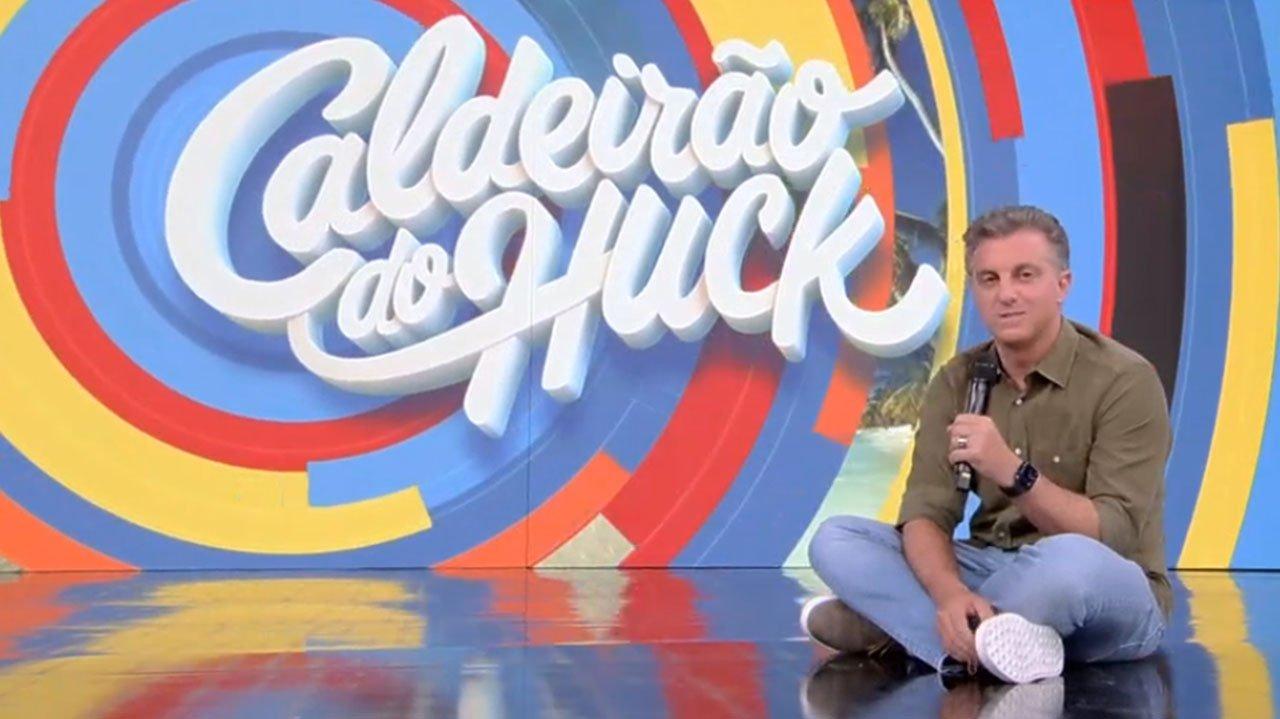 Luciano Huck sentado no palco no Caldeirão do Huck, diante do telão em que aparece a logo do programa