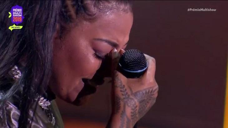 Ludmilla chora com uma mão no rosto.