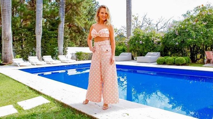 Eliana posa diante da piscina de sua mansão