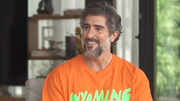Marcos Mion de camiseta laranja em entrevista para o Fantástico