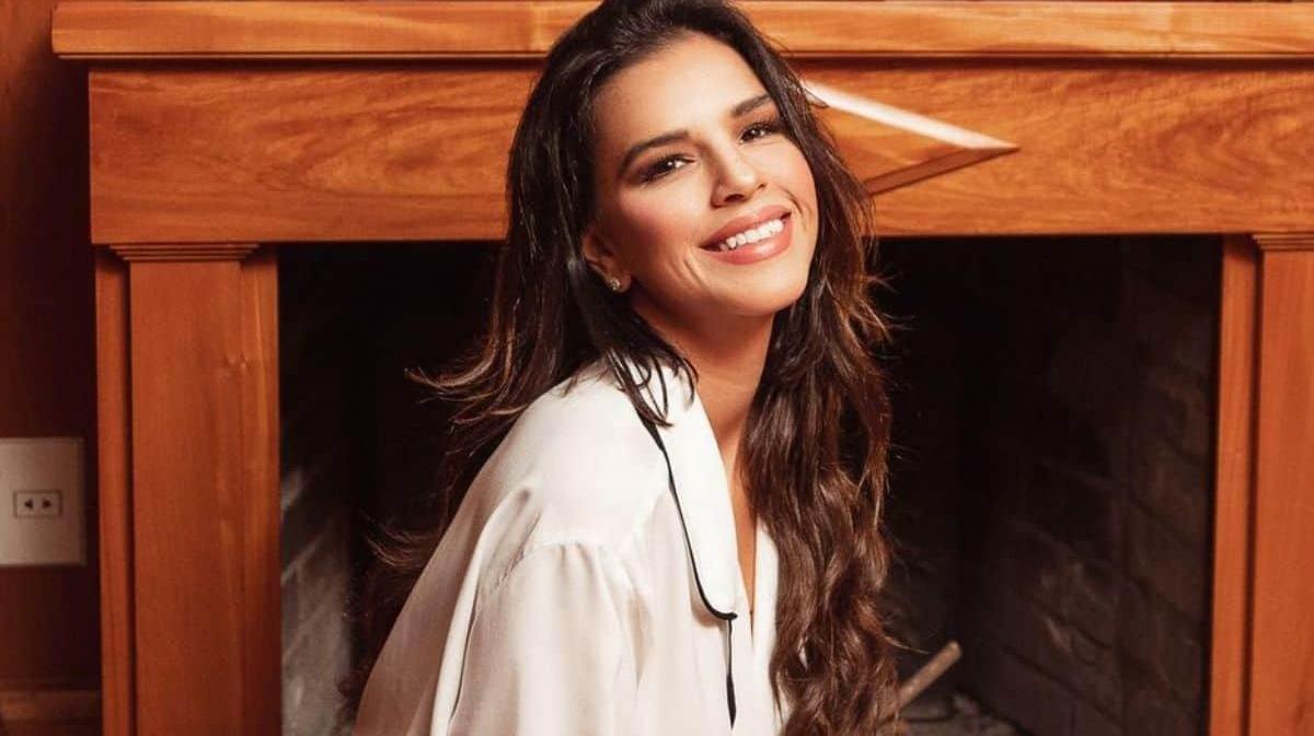Mariana Rios sorrindo com lareira ao fundo