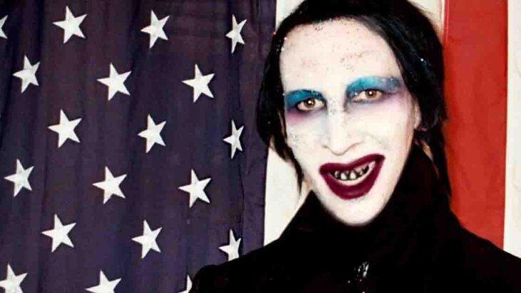 Marilyn Manson posado para foto, ao lado da bandeirados Estados Unidos