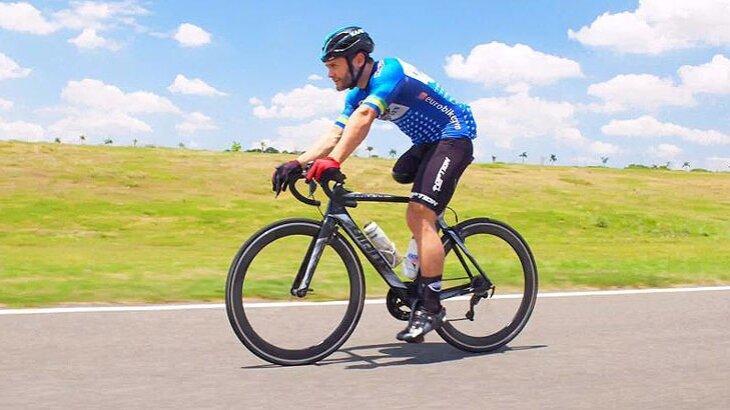 Atleta paralímpico praticando ciclismo em uma rodovia