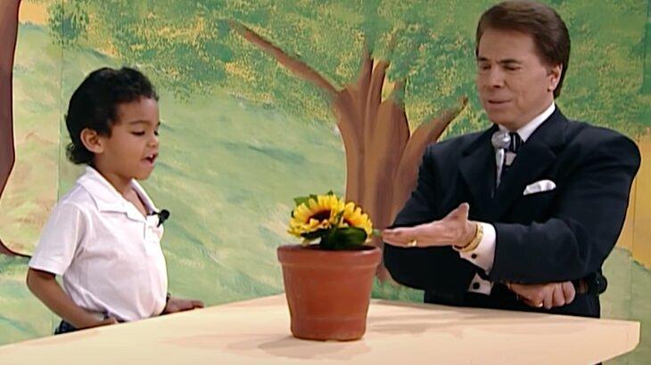 Menino conversa com flor artificial, sob a orientação de Silvio Santos, que aponta para o objeto sobre a mesa