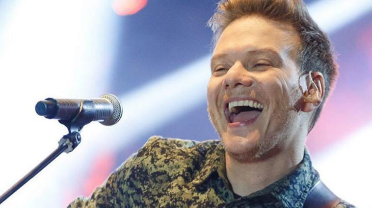 Michel Teló cantando e sorrindo