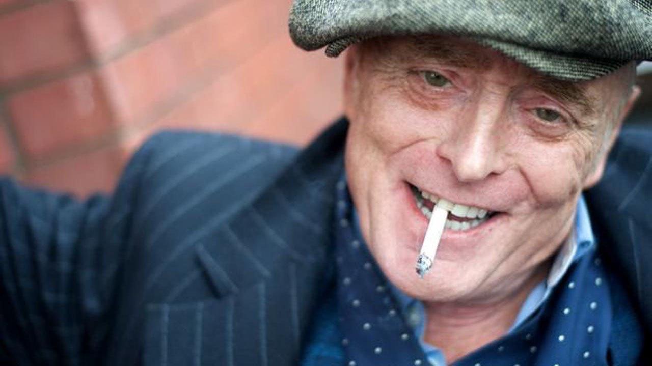 Brian Travers sorridente, com um cigarro na boca
