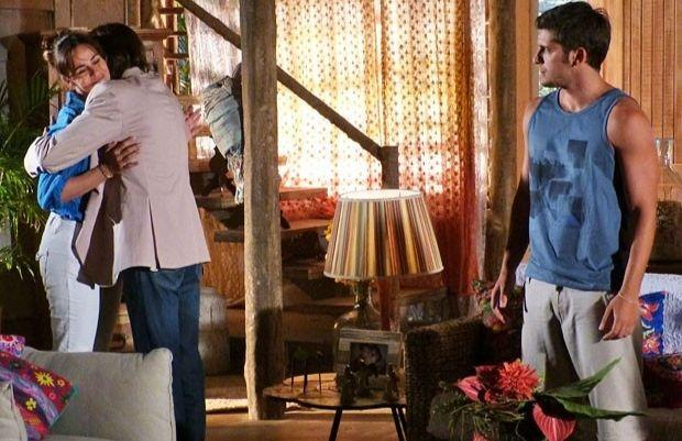 Reinaldo abraçando Natália enquanto  Juliano observa de longe em cena de Flor do Caribe