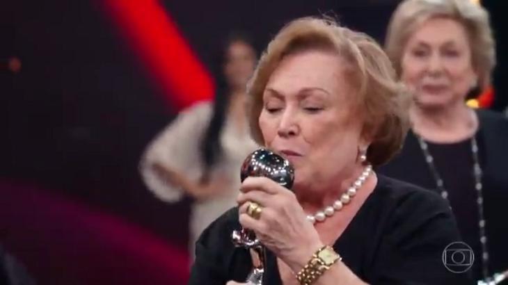 Nicette Bruno beijando um troféu no palco do Domingão