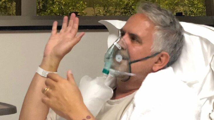 Orlando Morais acenando, com máscara de oxigênio, em leito hospítalar