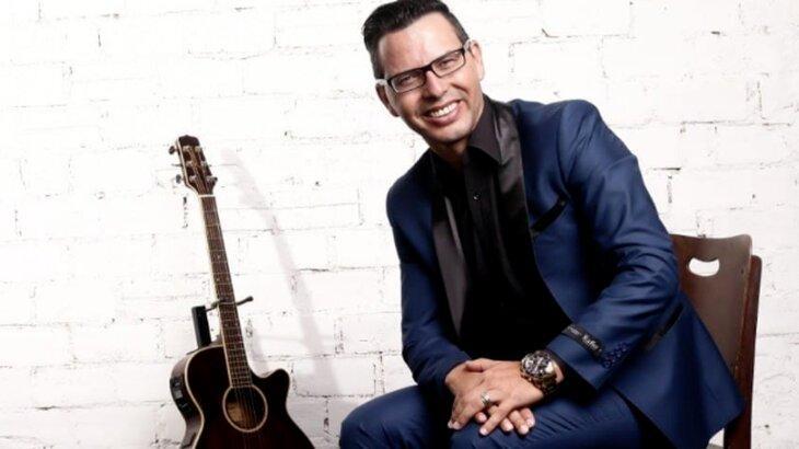 Oziel Rodrigues de Oliveira com violão ao lado, sentado, posado para foto