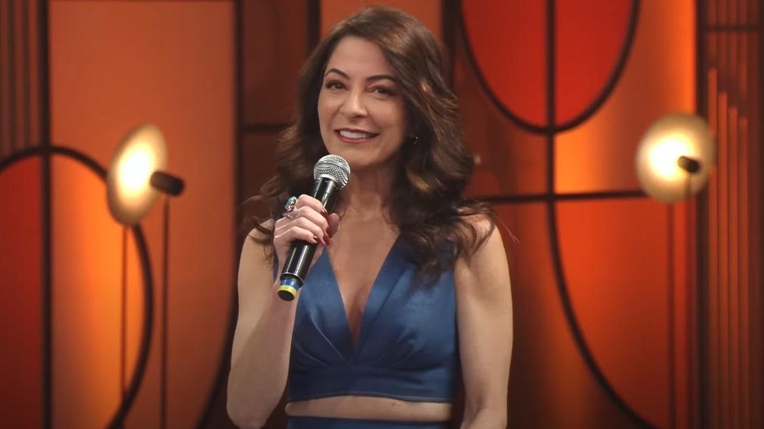 Ana Paula Padrão sorrindo de roupa azul segurando o microfone com a mão direita