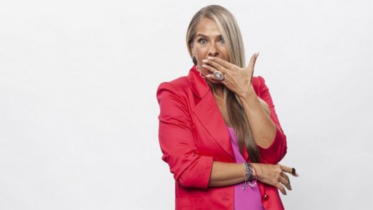 Adriane Galisteu posada com a mão na boca