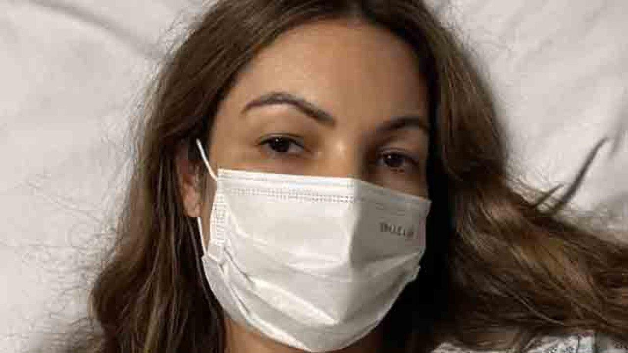Patrícia Poeta deitada na cama de hospital e de máscara